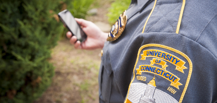 UConn Police Officer holding a cell phone